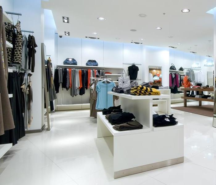 A retail store with white floors and clothing racks.